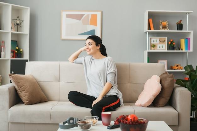 リビングルームのコーヒーテーブルの後ろのソファに座っている若い女性