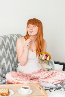 Молодая женщина, сидя на диване, есть завтрак овса granola Бесплатные Фотографии