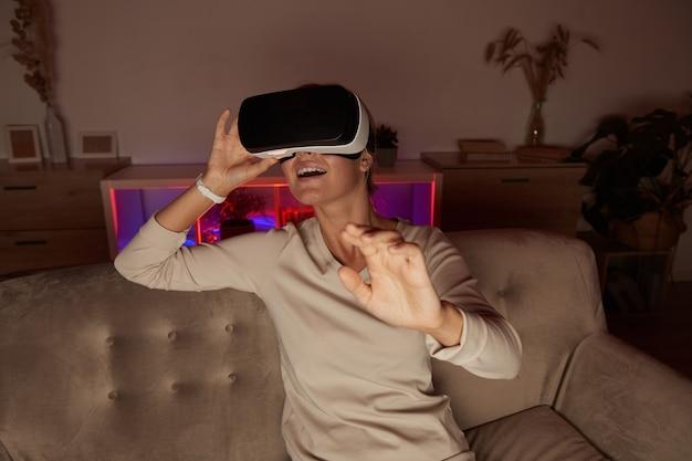 自宅で仮想ゲームで遊んで仮想メガネのソファに座っている若い女性