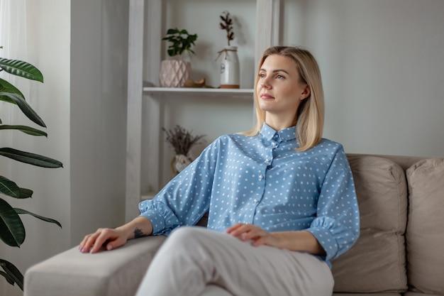 ソファに座って、窓を思慮深く見ている若い女性