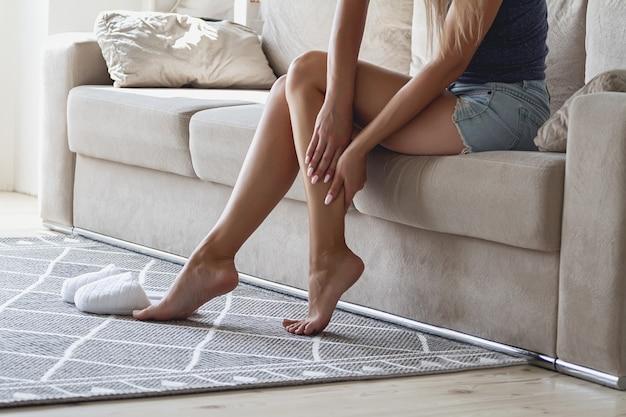 집에서 다리 통증으로 고통받는 소파에 앉아 젊은 여자