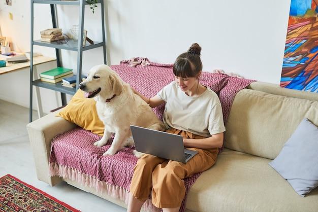 彼女の犬と一緒にソファに座って、自宅のラップトップでオンラインで作業している若い女性
