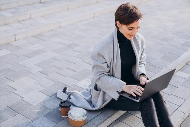 階段に座って、コンピューターで作業している若い女性