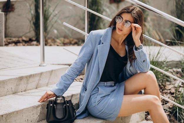 Молодая женщина, сидящая на лестнице в синем костюме