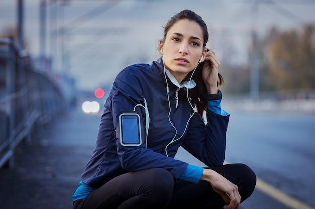 走って休んでいる通りに座っている若い女性