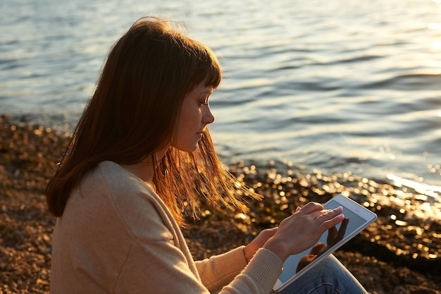 Молодая женщина сидит на пляже, на закате, читает с планшета