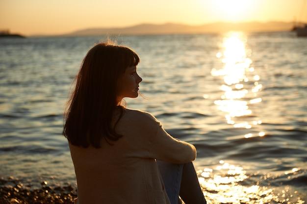 Молодая женщина, сидящая на пляже на закате