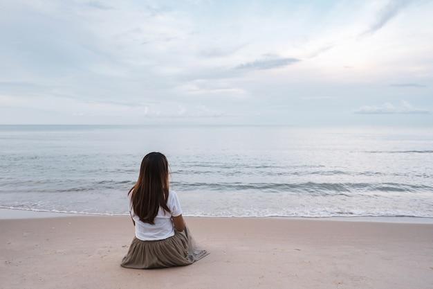 ビーチに座っている若い女性