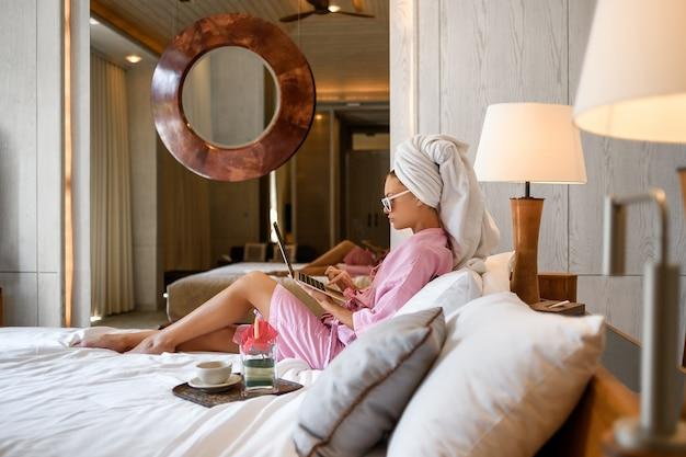 Молодая женщина сидя на кровати в современном интерьере спальни с ее компьтер-книжкой и работой. современный дизайн для спальни. отдых после рабочих дней.