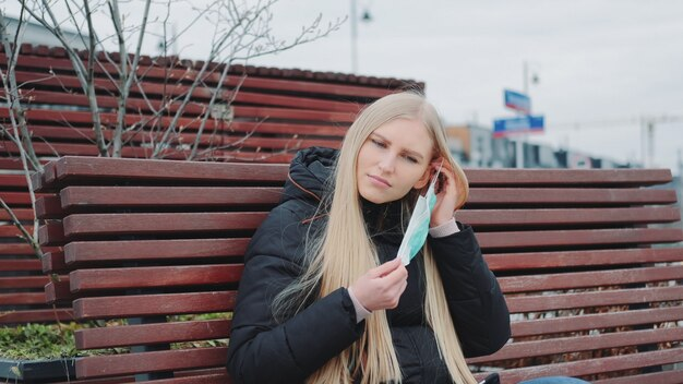 Молодая женщина сидит на скамейке и надевает защитную медицинскую маску на лицо