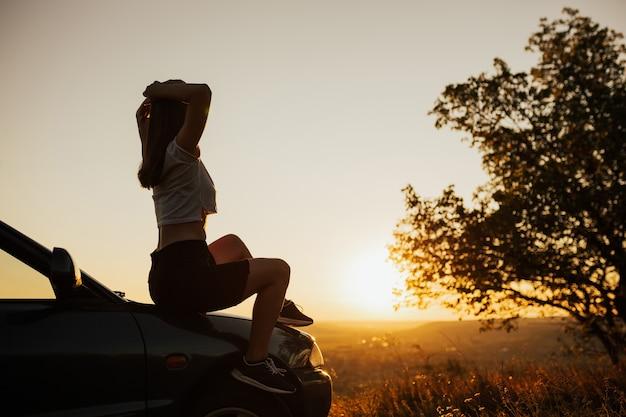 석양에 차에 앉아 젊은 여자. 그녀는 아름다운 풍경과 일몰을 즐기고 있습니다.