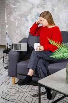 ノートパソコンの画面を見ながらソファに座っている若い女性。オンラインでコンピューターを使って仕事をしている、やる気のある在宅の女子学生フリーランサー。