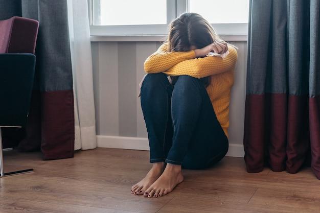パートナーに虐待された後、床に座っている若い女性。女性に対する暴力と虐待の概念。
