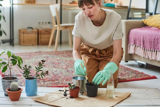 Молодая женщина сидит на полу и сажает растения в горшки в комнате