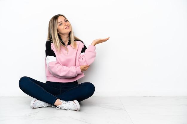 屋内の床に座って手を横に伸ばして招待する若い女性