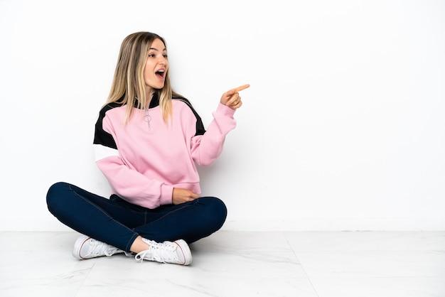 屋内で床に座って指を横に向けて製品を提示する若い女性