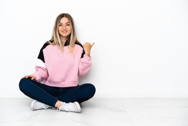 製品を提示するために横を指している屋内の床に座っている若い女性