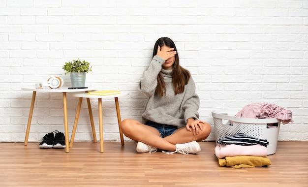 Молодая женщина, сидя на полу в помещении с корзиной для одежды, закрывающей глаза руками. не хочу что-то видеть