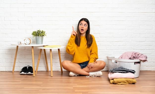 옷 바구니와 함께 실내 바닥에 앉아있는 젊은 여성이 손가락을 들어 올리면서 해결책을 실현하려고합니다.