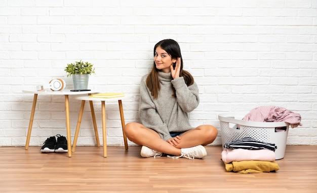 耳に手を置いて何かを聞いている洋服バスケットと屋内で床に座っている若い女性