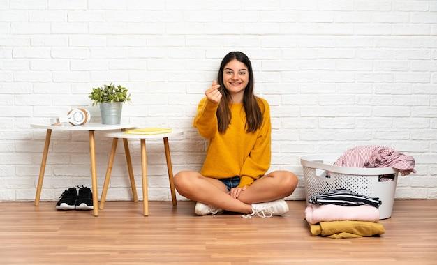 お金のジェスチャーを作る服のバスケットと屋内で床に座っていた若い女性