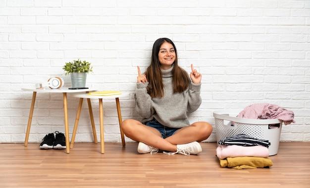 좋은 아이디어를 가리키는 옷 바구니와 함께 실내에서 바닥에 앉아 젊은 여자