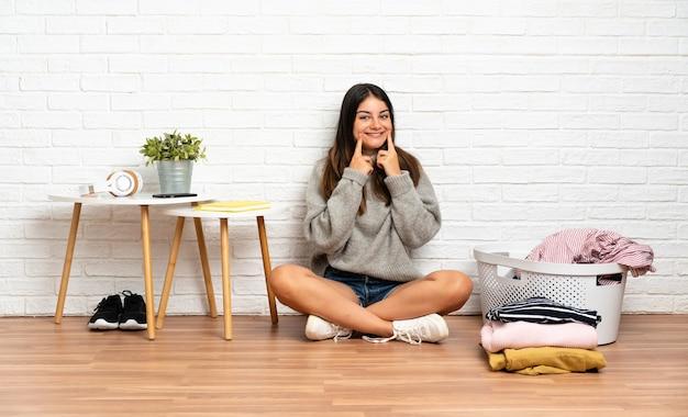 Молодая женщина сидит на полу в помещении с корзиной для одежды, улыбаясь счастливым и приятным выражением лица