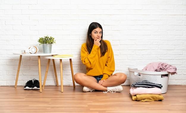 Молодая женщина, сидящая на полу в помещении с корзиной для одежды, удивлена и шокирована, глядя вправо
