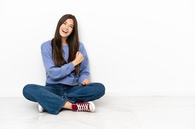승리를 축 하하는 바닥에 앉아 젊은 여자