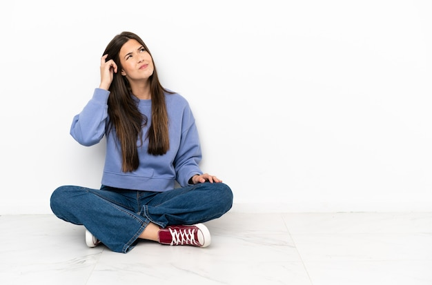 의심을 가지고 혼란스러운 얼굴 표정으로 바닥에 앉아 젊은 여자