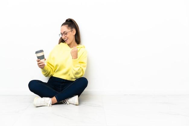 勝利を祝うテイクアウトコーヒーを持って床に座っている若い女性