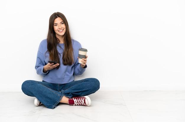 멀리 데리고 커피를 들고 바닥에 앉아 젊은 여자와 모바일