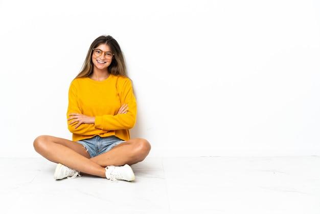腕を正面の位置に交差させたままで隔離された床に座っている若い女性
