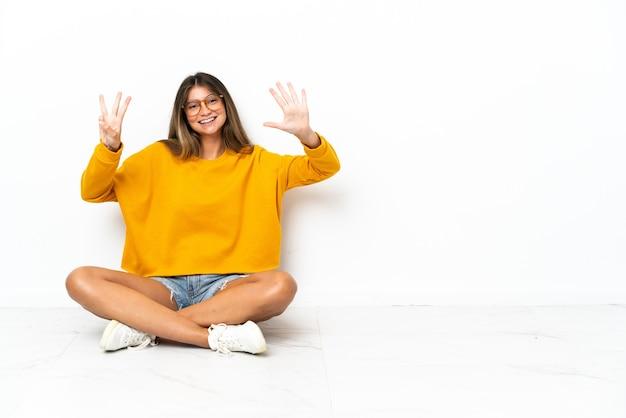 손가락으로 여덟 세 흰색 배경에 고립 된 바닥에 앉아 젊은 여자