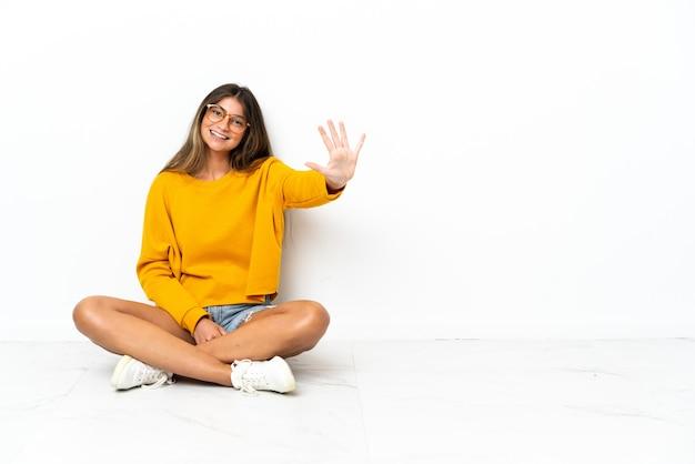 손가락으로 5 세 흰색 배경에 고립 된 바닥에 앉아 젊은 여자
