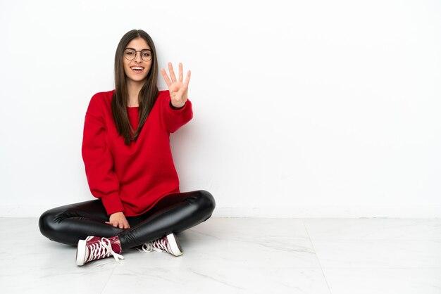 흰색 배경에 격리된 바닥에 앉아 손가락으로 4를 세는 젊은 여성