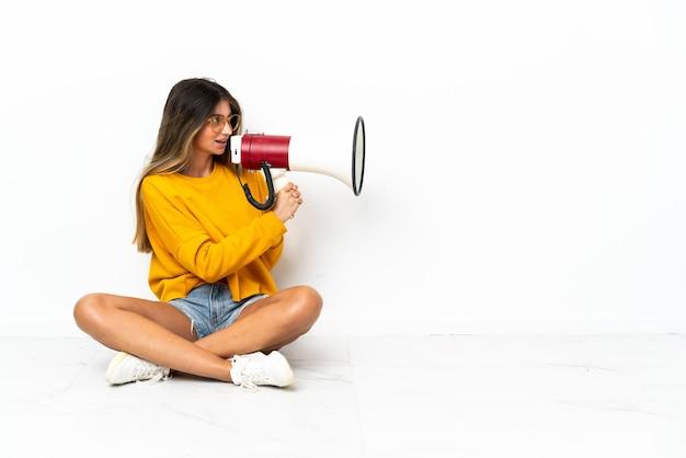 Молодая женщина, сидящая на полу, изолированная на белом фоне, кричит в мегафон