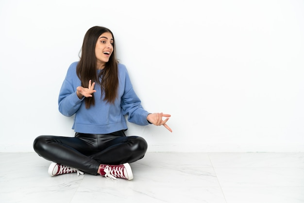 Молодая женщина, сидящая на полу на белом фоне с удивленным выражением лица