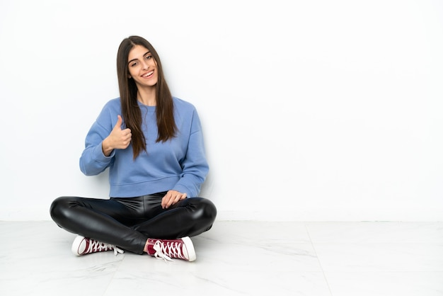 Молодая женщина сидит на полу на белом фоне с большими пальцами руки вверх, потому что произошло что-то хорошее
