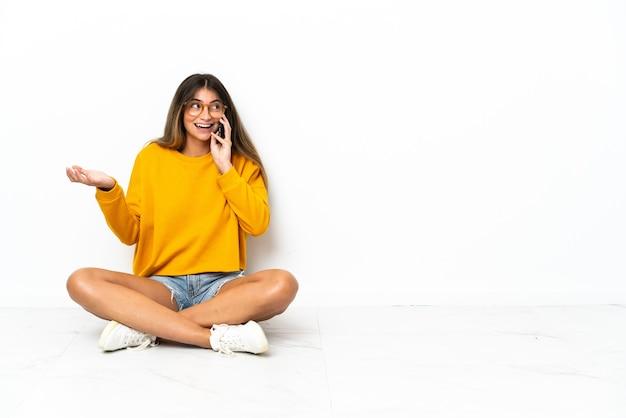 누군가와 휴대 전화로 대화를 유지하는 흰색에 고립 된 바닥에 앉아 젊은 여자
