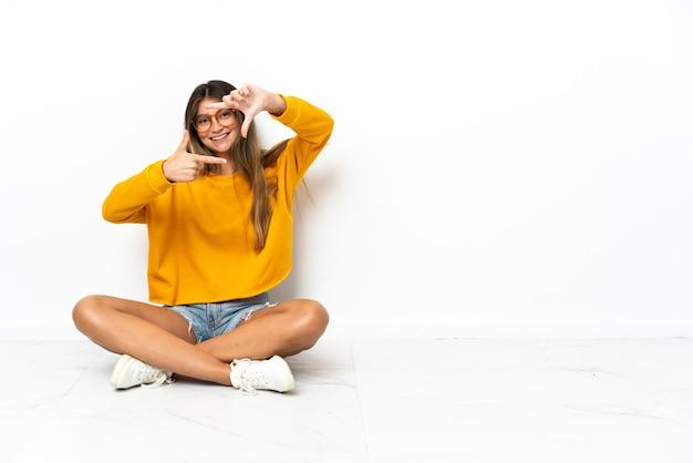 顔に焦点を当てる白い壁で隔離の床に座っている若い女性。フレーミングシンボル
