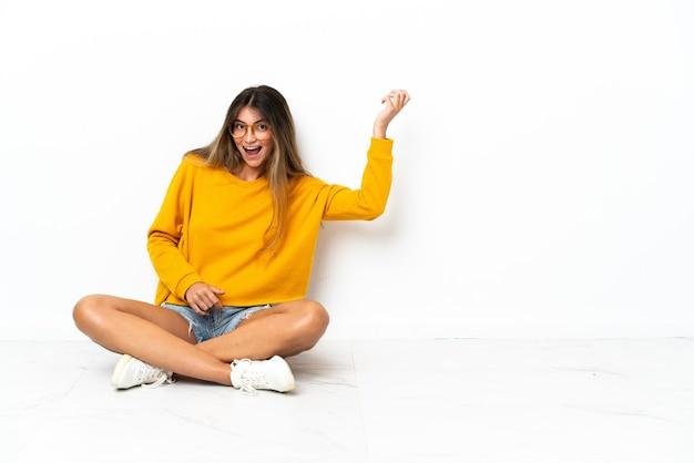 Молодая женщина, сидящая на изолированном полу