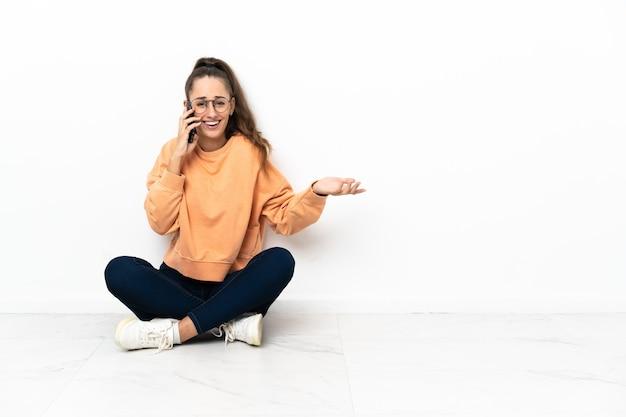 누군가와 휴대 전화로 대화를 유지하는 바닥에 앉아 젊은 여자
