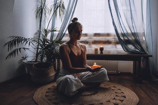 フロアライトキャンドルに座っている若い女性は、瞑想を楽しんでいます自宅でヨガの練習をしますメンタル
