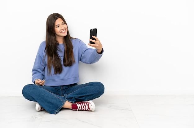 젊은 여자는 selfie를 만드는 바닥에 앉아