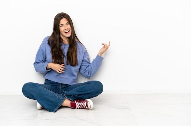 기타 제스처를 만드는 바닥에 앉아 젊은 여자