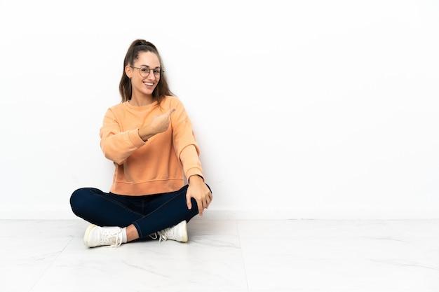 Молодая женщина, сидящая на полу, указывая назад