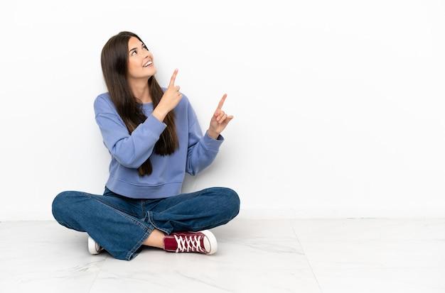 床に座って人差し指で指している若い女性は素晴らしいアイデア