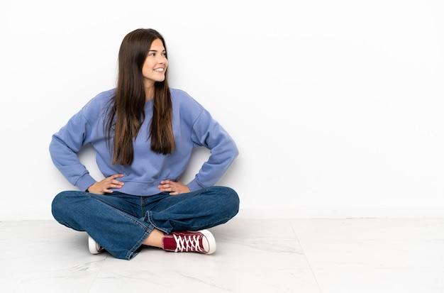 엉덩이에 팔을 포즈와 미소 바닥에 앉아 젊은 여자
