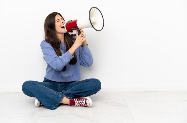 Молодая женщина сидит на полу и кричит в мегафон